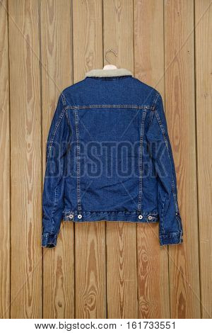 Back jean jacket is on clothes-hanger on wooden background