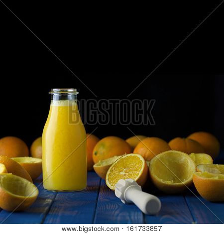 Freshly squeezed organic orange juice in bottle with ripe organic oranges on blue wood boards against plain pure black background. Selective focus. Empty space. Negative space. Copy space. Concept of healthy lving. Concept of organic food. Concept of deto