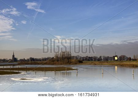 Frozen river foreland from the river Maas near the Dutch village Batenburg with the church tower and the windmill in the background