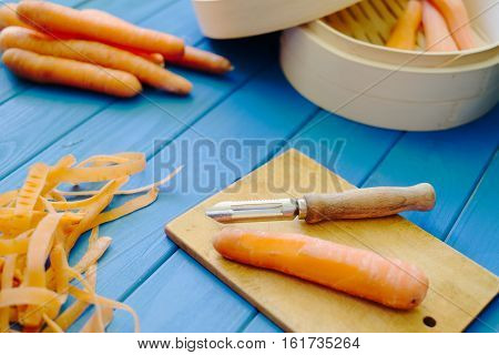 Peeled orange carrot on wood cutting board on blue background. Peels peeler and bamboo steamer. Concept of preparation of baby food.