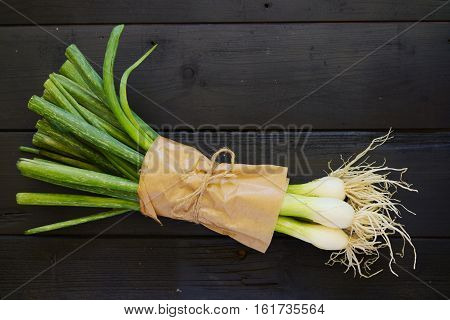Raw food ingredients bouqet of spring onions on black boards. Top down. Flat lay.