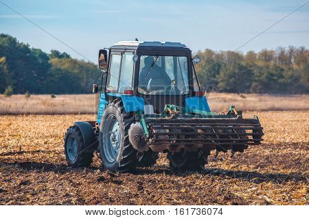 Big blue tractor plows the field and removes the remains of previously mown sunflower. Part of the cultivator steel round discs in a row close-up. Work agricultural machines. Harvest.