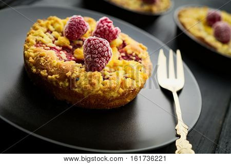 Sweet homebaked raspberry jam crumble tart with frozen raspberries on black plate on black wood boards with gold fork. Selective focus on the front raspberry. Concept of home baking.