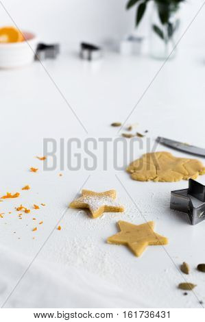 Making Christmas Biscuits Flavoured with Orange Zest and Ground Cardamom on White Table
