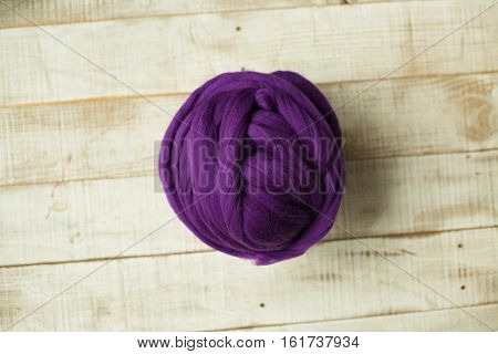 Purple merino wool ball on wooden background