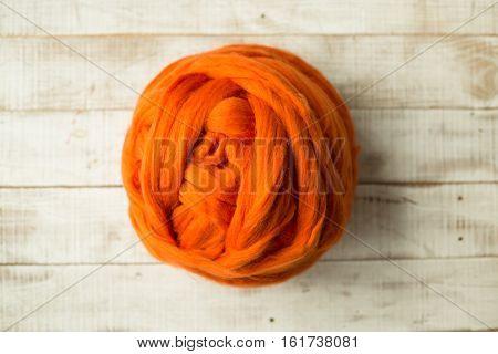 Orange merino wool ball on wooden background