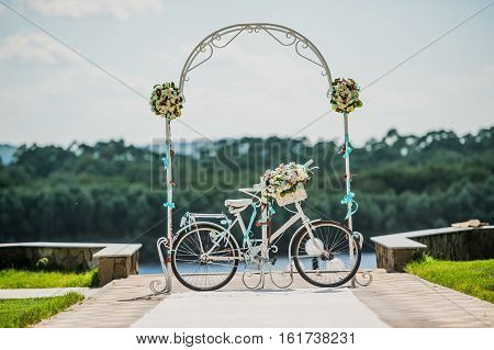 White and blue arch decorated with flowers bycicle, wedding registration outdoors.