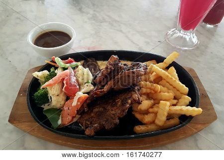Tasty and delicious grilled lamb chop with vegetables and fries for side dishes served on a hotplate