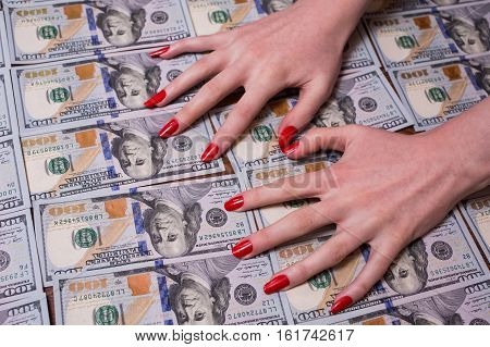 woman's hands with red nails lying on the money greed for money background of the money hundred dollar bills front side. background of dollars new hundred-dollar bil face the evolution of the bill in one hundred dollars
