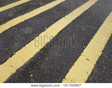 Full frame yellow stripes road markings on black tar road.