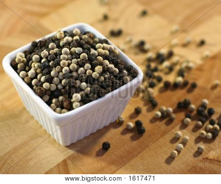 Whole Black And White Pepper On Cutting Board