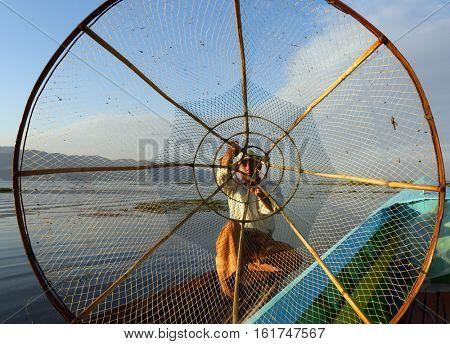 Myanmar travel attraction landmark - Traditional Burmese fisherman with fishing net at Inle lake in Myanmar