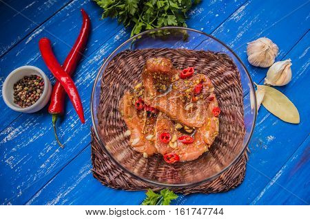 Marinated meat with spices and red pepper. Wooden blue background. Top view