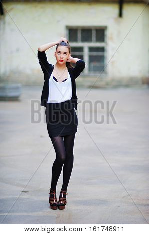 beautiful girl with long hair in a white shirt and a black cardigan and black mini-skirt and black pantyhose walking down the street and straightens hair