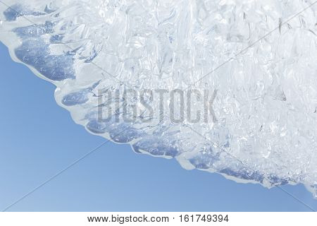 Whimsical surface ice closeup on blue sky background. Copy space. Texture.