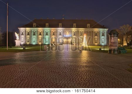 The photograph shows a historic palace in Zagan in western Poland. It's night. The palace is illuminated by electric lamps. At the palace you can see elements of the Christmas decorations.