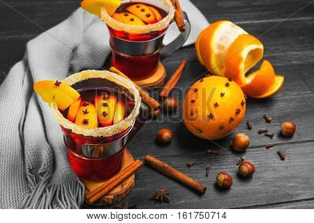 Traditional Christmas winter beverage drink mulled wine on Dark Black background. Glasses with mulled wine wrap gray knit scarf. Ingredients for drink mulled wine hazelnut cinnamon cloves orange star anise.