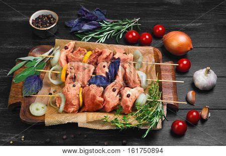 Cooking Raw Marinated pork in kebabs. Ingredients for meat kebabs basil rosemary thyme tomatoes onions garlic. Meat kebabs on skewers. Black wood background.