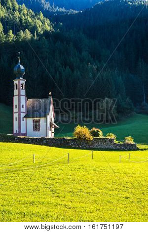 Tirol, Dolomites. The church of Santa Maddalena in valley Val di Funes. Forested mountains surrounded by green Alpine meadows. Sunny warm autumn
