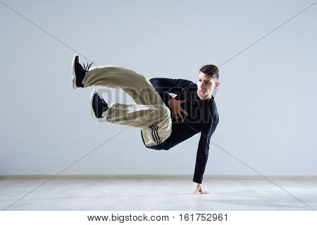 Hip hop dancer performing isolated over white background. Hip hop performer is standing in plank.