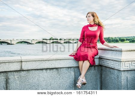 Young woman in red dress and scarf sitting on stone railing in Washington DC