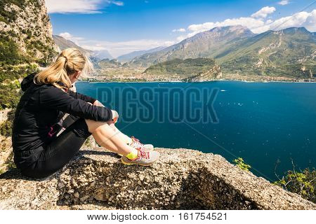 Young sporty woman admire the panorama from the Ponale trail in Riva del Garda Italy.