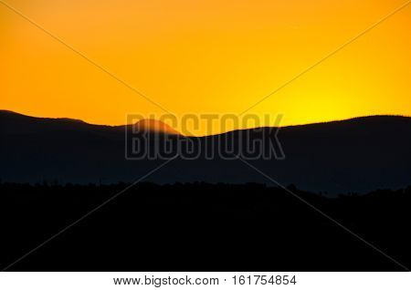 A colorful sunset in Santa Fe New Mexico with a sun hiding behind mountains.