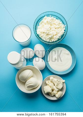Protein products: cheese, cream, milk, eggs on the blue background. Top view.