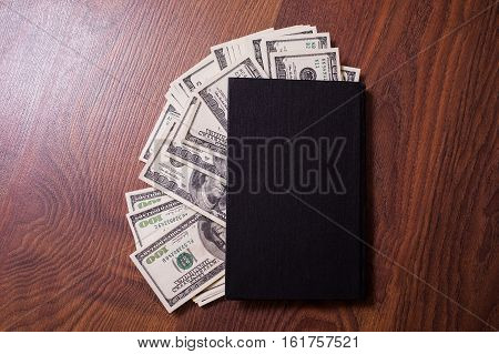 black book and money. business plan money background hundred dollar bills front side. background of dollars money in the black book the work of a writer