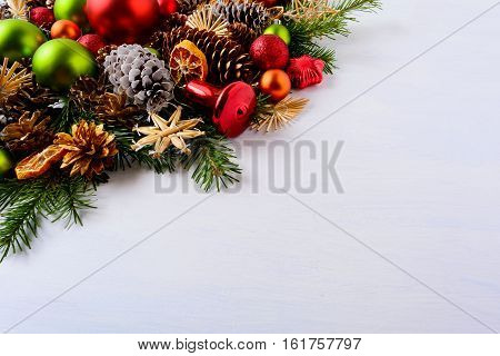 Red and green Christmas ornaments fir branches and pine cones. Christmas decoration with jingle bell and dried orange slices. Christmas greeting background. Copy space.