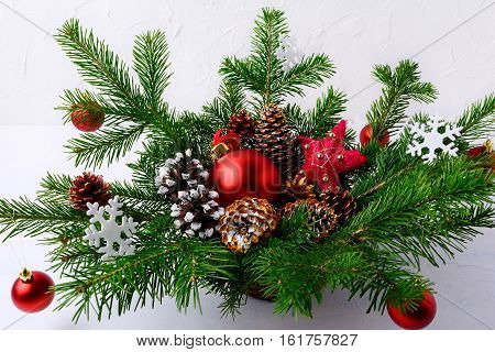 Christmas table centerpiece with red balls and hand decorated pine cones. Christmas decoration with fir branches and red baubles. Christmas greenery with ornaments in wicker basket.