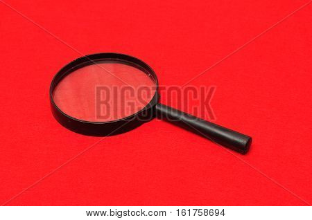 Magnifying glass isolated on a red background
