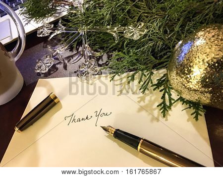 Christmas Cards with a Fountain pen on desk writing thank you to community with laptop computer and golden Christmas ornaments, evergreen tree branches and decorations And note cards for and seasons greetings or year end message for the holiday season