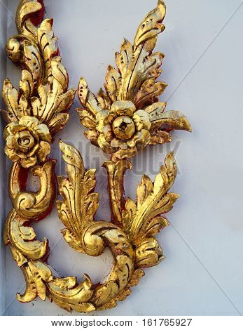 Thai style wooden carved - golden flower on white wall