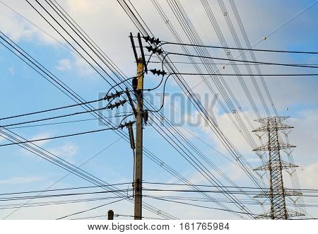 Electrical pole and pylon with power lines against blue sky