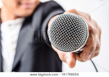 Businessman making speech with microphone and hand gesturing concept for explaining protesting or belief