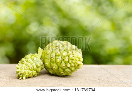 Noni fruit  on wooden table and green background.Fruit for health and herb for health.