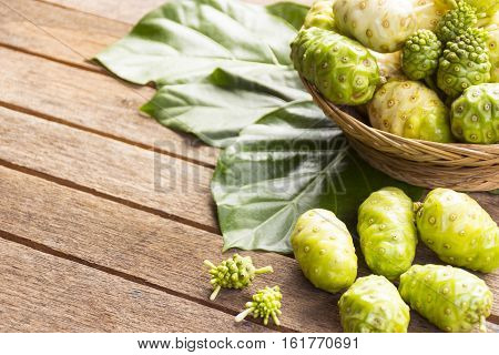 Noni fruit  and noni in the basket on wooden table.Zoom in01