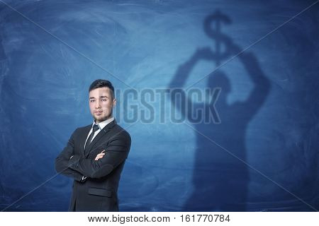 Businessman standing with his hands across and a shadow on the blackboard behind him holding a dollar sign above his head. Prosperous well-being. Financial fund. Making money