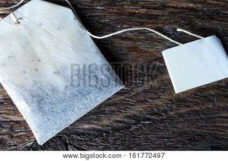 A top view image of a rectangular shaped tea bag on a wooden surface.