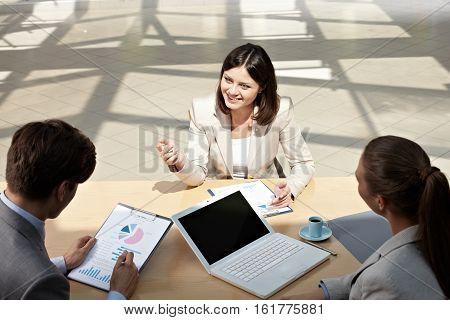 Young businesswoman explaining business task to her subordinates