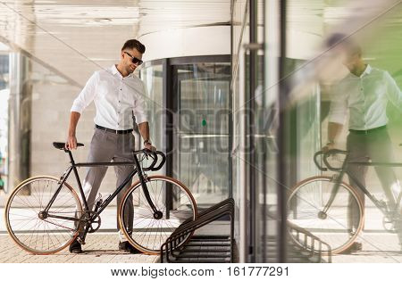 business, lifestyle, transport and people concept - young man parking bicycle on city street