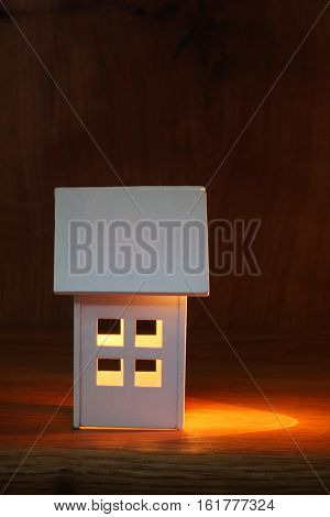 Painted model wooden  house with light shining to one side for effect. Concept of new home with space for text.
