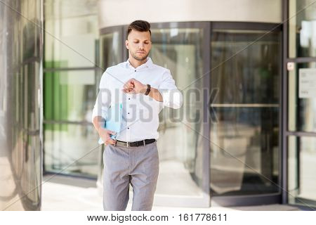 business, time and people concept - young man with folder looking at wristwatch on city street