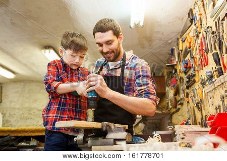 family, carpentry, woodwork and people concept - father and little son with drill perforating wood plank at workshop