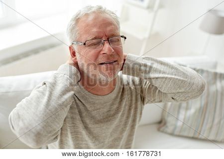healthcare, pain, stress, age and people concept - senior man suffering from neckache at home