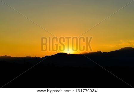 The orange light of sunset behind the mountain.
