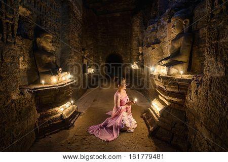 Beautiful Asian burma women making offerings of incense candles to a Buddha Pagoda at Mrauk-u Myanmar