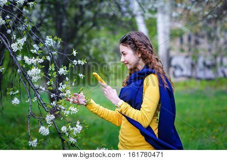beautiful young woman walking in the park with your phone.