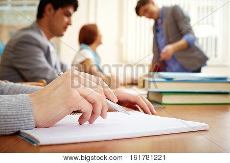 Female hands writing in workbook in college